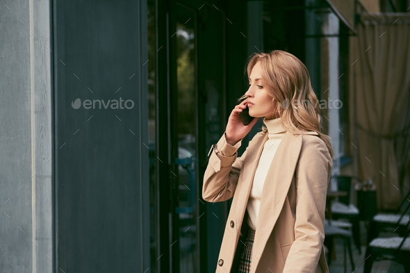 Side view of attractive blond girl in trench coat thoughtfully talking on cellphone outdoor - Stock Photo - Images