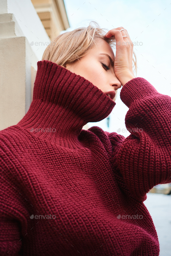 Close up sensual blond girl in knitted sweater emotionally posing outdoor - Stock Photo - Images