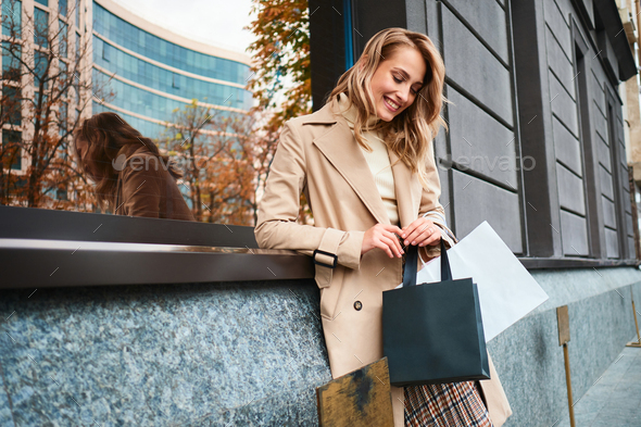Portrait of pretty joyful blond girl in beige coat with shopping bags on city street - Stock Photo - Images