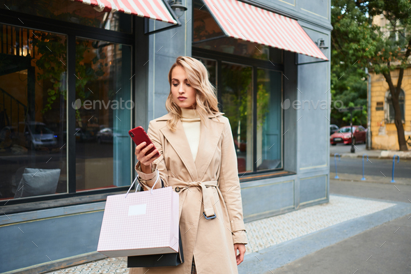 Beautiful casual blond girl in stylish trench coat with shopping bags using cellphone on city street - Stock Photo - Images