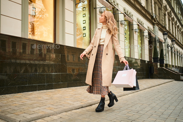 Attractive stylish blond girl in beige coat with shopping bags dreamily looking at store window - Stock Photo - Images