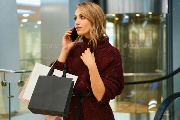 Attractive blond girl in knitted sweater thoughtfully talking on cellphone in shopping mall - Stock Photo - Images