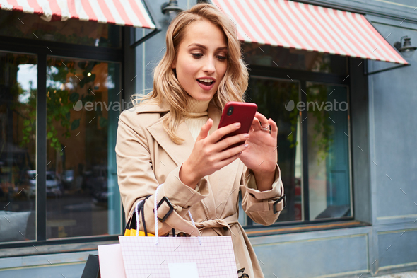 Surprised blond girl in stylish trench coat with shopping bags happily using cellphone on street - Stock Photo - Images