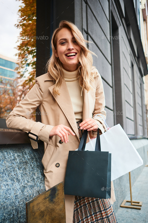 Pretty cheerful stylish blond girl in beige coat with shopping bags happily laughing on street - Stock Photo - Images
