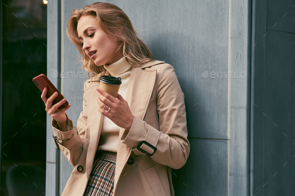 Attractive casual blond girl in trench coat with coffee to go dreamily using cellphone outdoor - Stock Photo - Images