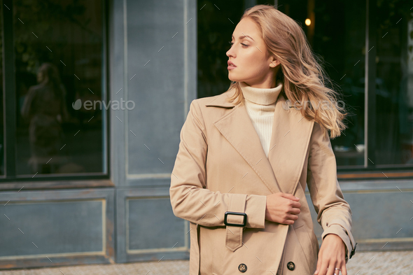 Side view of attractive blond girl in trench coat confidently looking away on street - Stock Photo - Images