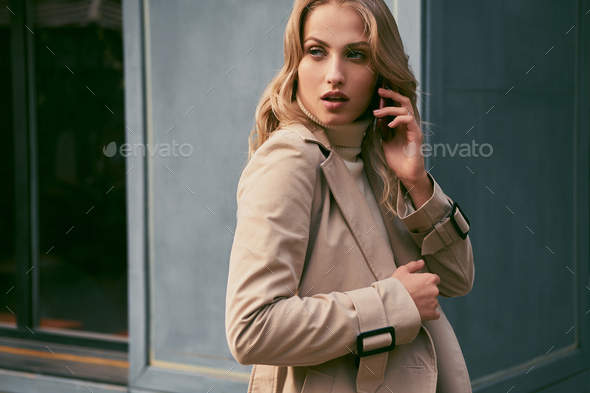 Attractive casual blond girl in trench coat talking on cellphone sensually looking away outdoor - Stock Photo - Images