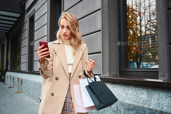 Beautiful stylish blond girl in beige coat with shopping bags using cellphone on street - Stock Photo - Images
