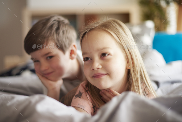 Little brother and sister in bed - Stock Photo - Images