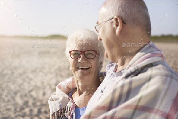 Senior couple warming up under the blanket - Stock Photo - Images