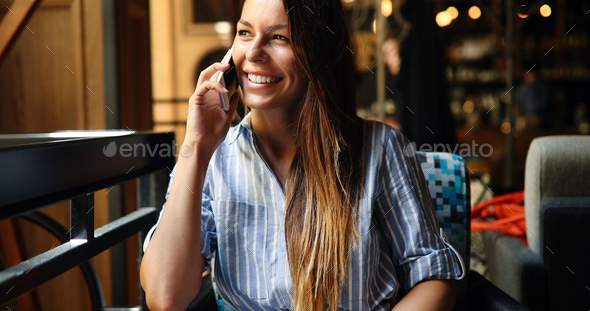 Beautiful woman talking on phone in restaurant - Stock Photo - Images