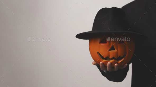 Jack o Lantern holding his pumpkin head with hat in hand - Stock Photo - Images