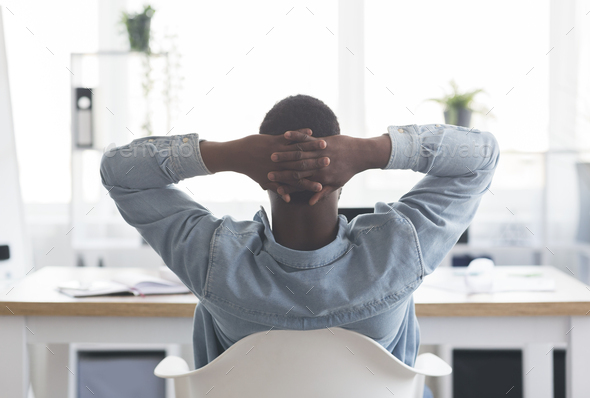 African american worker resting at workplace, leaning back on chair - Stock Photo - Images