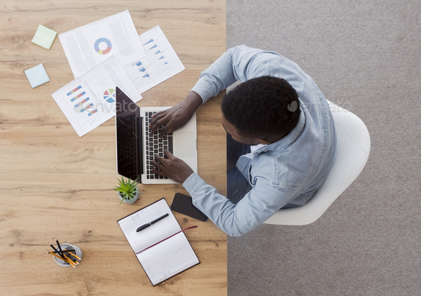 Top view of black employee working on laptop in office - Stock Photo - Images