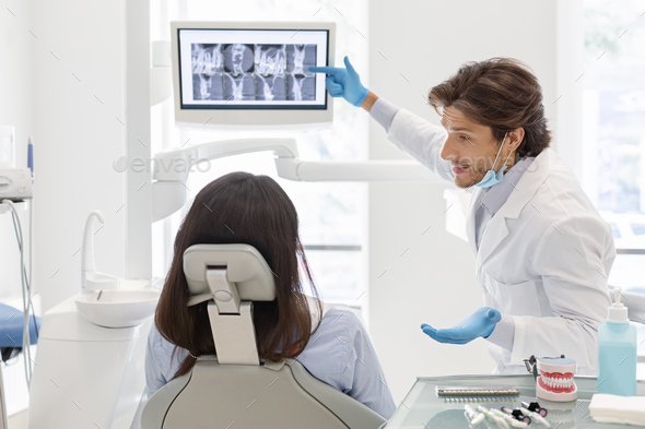 Dentist doctor explaining his patient x-ray results - Stock Photo - Images