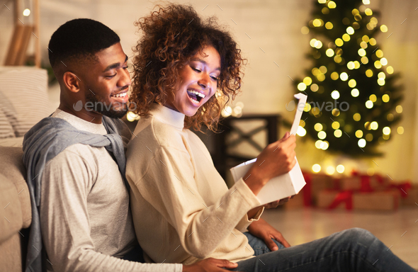Excited african-american couple opening xmas gift at home - Stock Photo - Images
