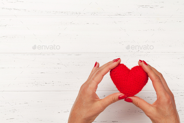 Woman hands holding red heart toy - Stock Photo - Images