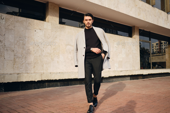 Young handsome stylish man in coat confidently looking in camera walking outdoor - Stock Photo - Images
