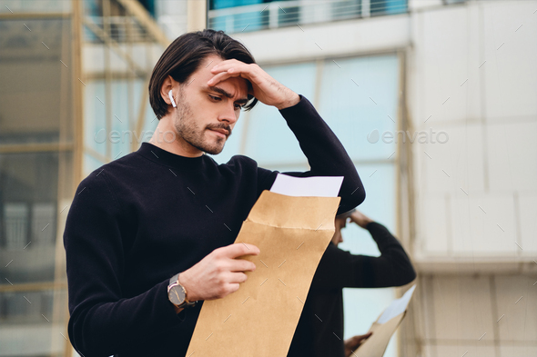 Young sad brunette man thoughtfully reading envelope with response outdoor - Stock Photo - Images