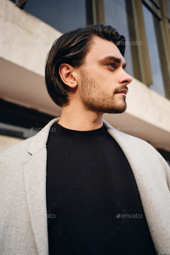 Side view of attractive casual brunette man in coat thoughtfully looking away outdoor - Stock Photo - Images
