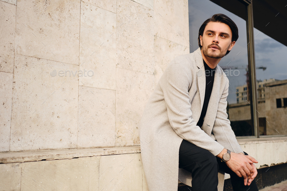 Young confident stylish man in coat intently looking away outdoor - Stock Photo - Images