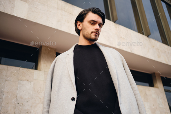 Young attractive stylish brunette man in coat slyly looking in camera outdoor - Stock Photo - Images