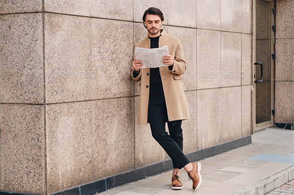 Young handsome confident man in beige coat thoughtfully reading newspaper outdoor - Stock Photo - Images