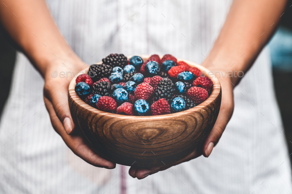 Holding a plate full of berries. Breakfast mix. Raspberries, blueberries, blackberries. plate - Stock Photo - Images