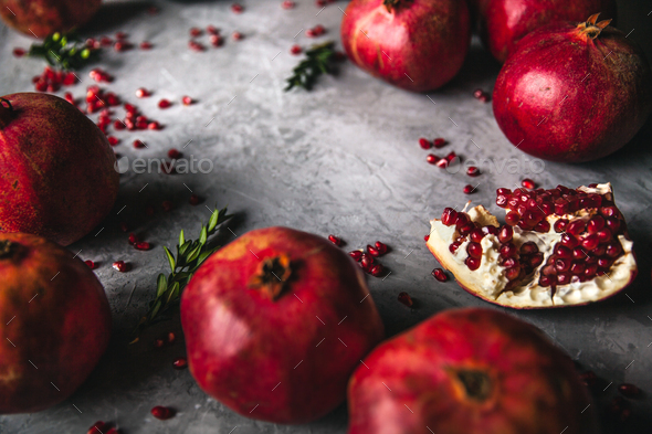 Pomegranate fruit. Ripe and juicy pomegranate on rustic grey background - Stock Photo - Images
