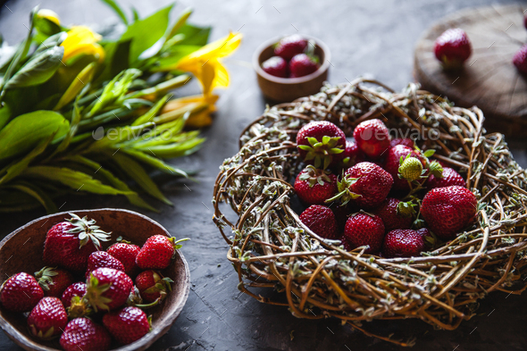 Delicious strawberries with yellow flowers on a dark gray background in a vintage wreath. Healthy - Stock Photo - Images