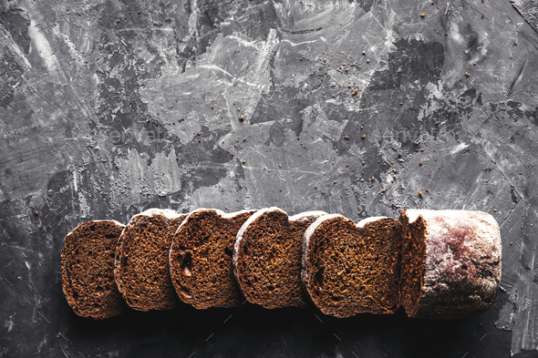 Sliced homemade white wheat bread with wheat flour on old black oven tray as background. Top view - Stock Photo - Images