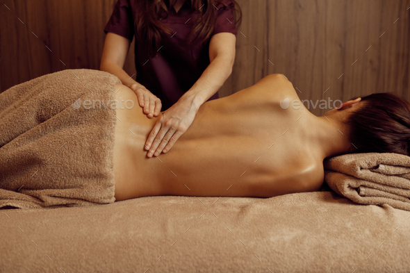 Female masseur pampering ribs to young slim woman - Stock Photo - Images