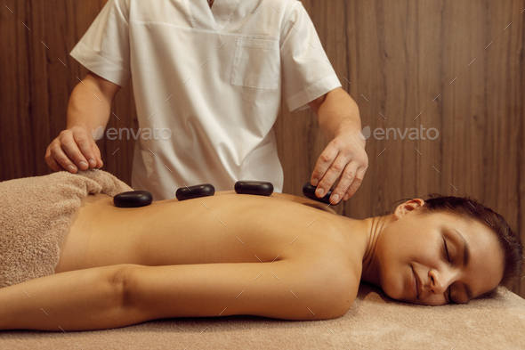 Male masseur puts stones on back of slim woman - Stock Photo - Images