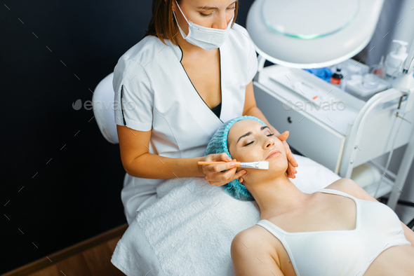 Cosmetician with brush cleans facial skin - Stock Photo - Images