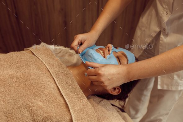 Masseur removes the cream mask from face of woman - Stock Photo - Images