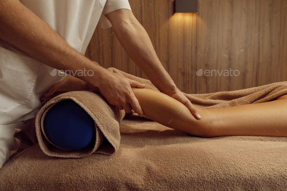 Male masseur stretching legs to young woman - Stock Photo - Images