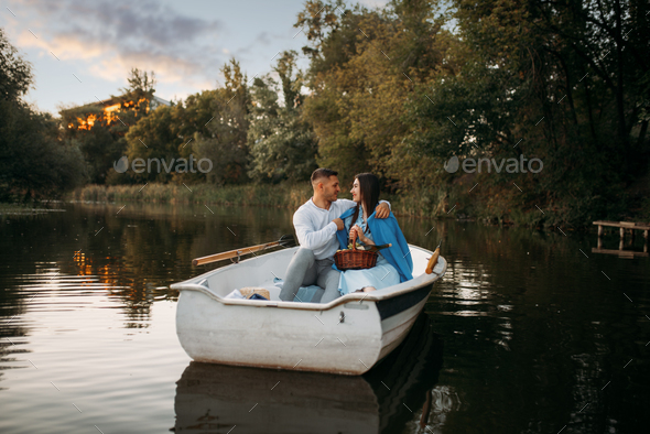 Love couple hugs in a boat on quiet lake at sunset - Stock Photo - Images