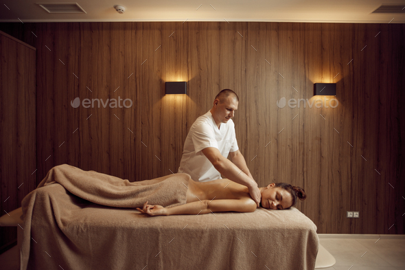 Male masseur pampering neck to young woman - Stock Photo - Images