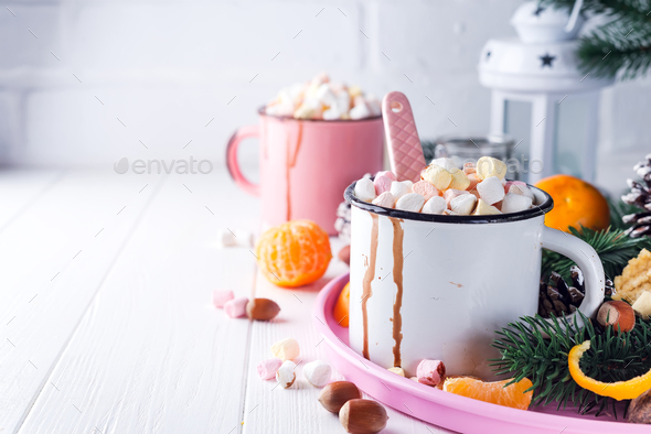 Cups of hot chocolate with marshmallows, mandarin, fir tree branches and nuts on white wooden - Stock Photo - Images
