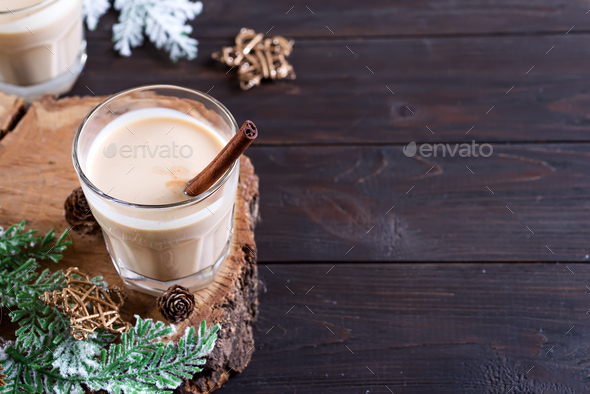 Eggnog Christmas milk cocktail, served in two glasses on a wood cutting board with fir branch and - Stock Photo - Images