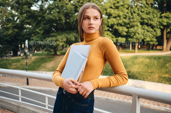 Attractive casual student girl with laptop and book thoughtfully looking away in city park - Stock Photo - Images