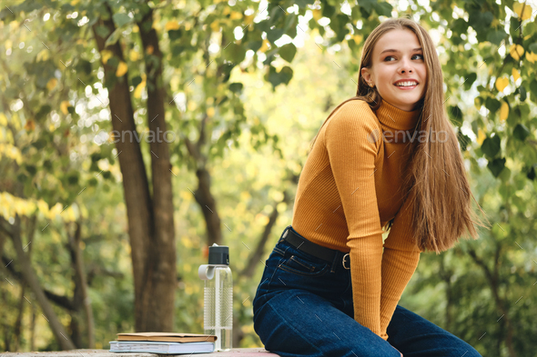 Pretty joyful casual student girl happily looking away in park - Stock Photo - Images