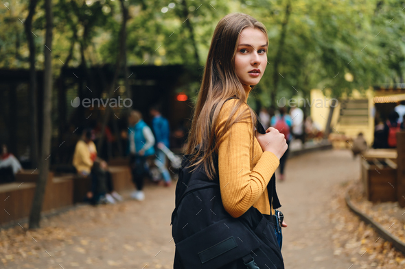 Beautiful casual student girl with backpack intently looking in camera in city park - Stock Photo - Images