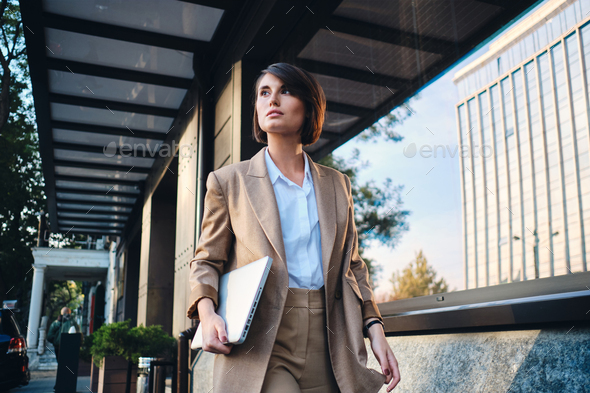 Young attractive stylish businesswoman with laptop thoughtfully walking on street - Stock Photo - Images