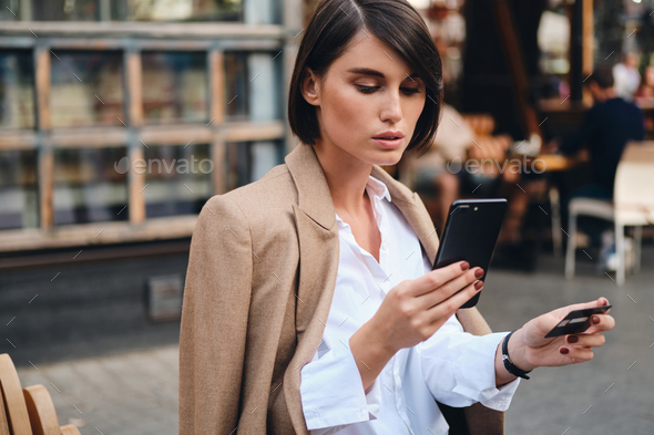 Young beautiful stylish businesswoman with credit card confidently using cellphone in cafe on street - Stock Photo - Images