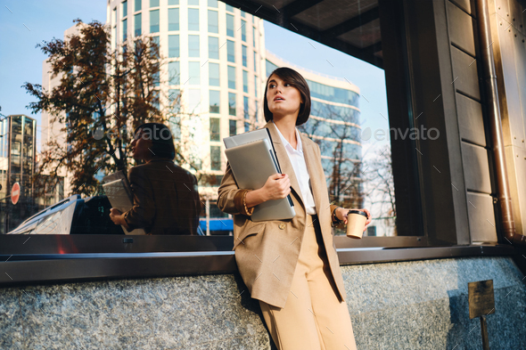 Young beautiful stylish businesswoman with laptop and coffee to go waiting on city street - Stock Photo - Images