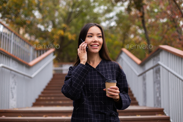 Young pretty casual woman in coat with coffee to go talking on cellphone happily walking in park - Stock Photo - Images