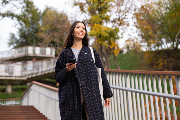 Young pretty smiling woman in coat with cellphone dreamily looking away in city park - Stock Photo - Images