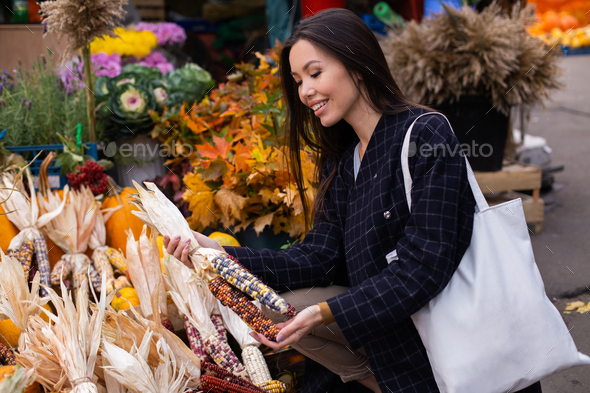 Young beautiful woman happily buying colorful corn for Halloween day at autumn farm shop outdoor - Stock Photo - Images