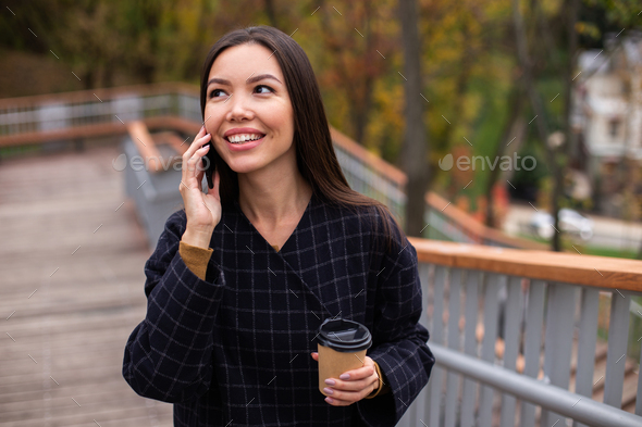 Young cheerful casual woman in coat with coffee to go happily talking on cellphone in park - Stock Photo - Images